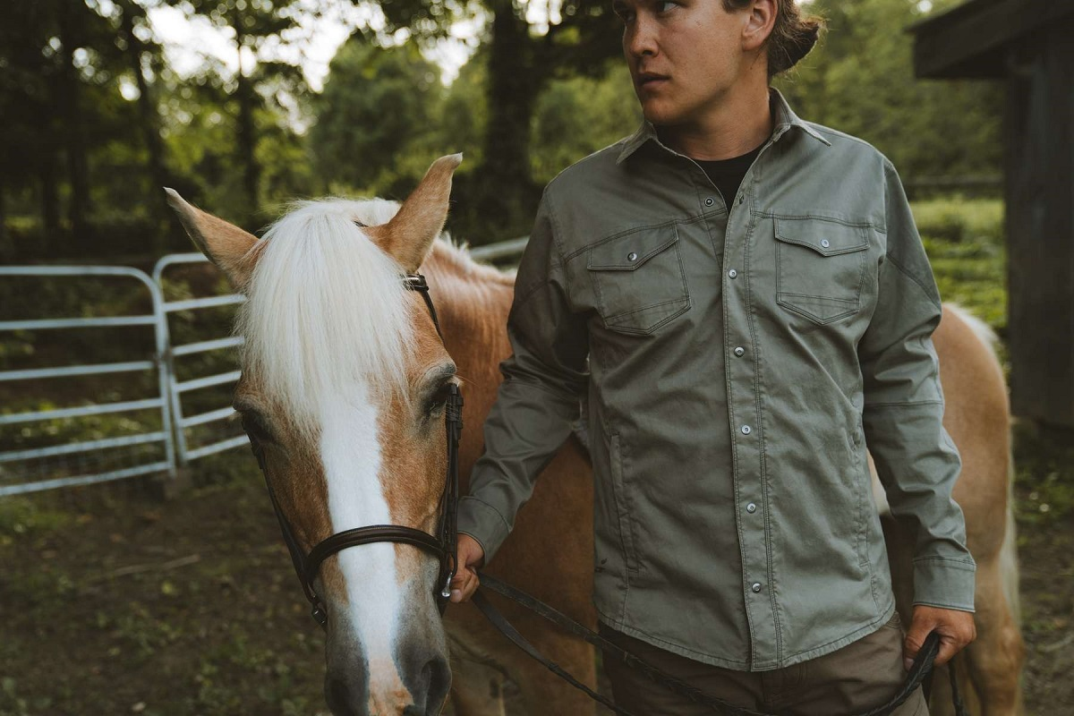 A man in a jacket holding a horse