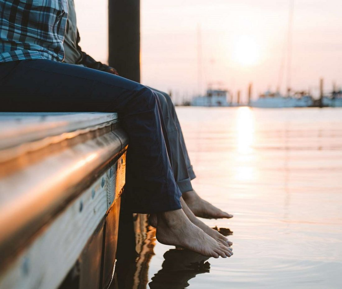 two people sitting at dock with feet touching body of water