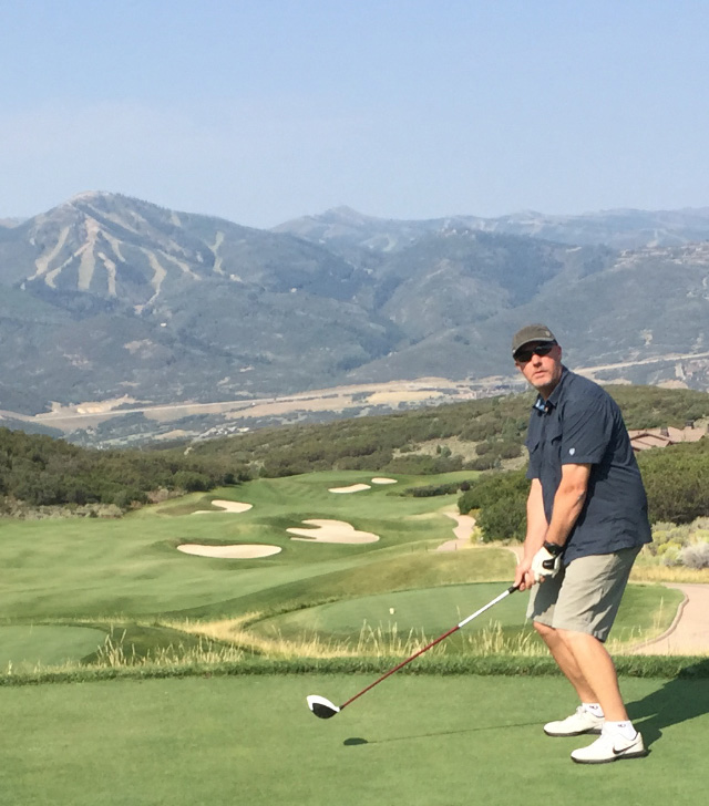 KUHL Sponsored Golf Course Hole - A man dressed in KUHL Golf Shorts taking a swing with a mountainside in the back.