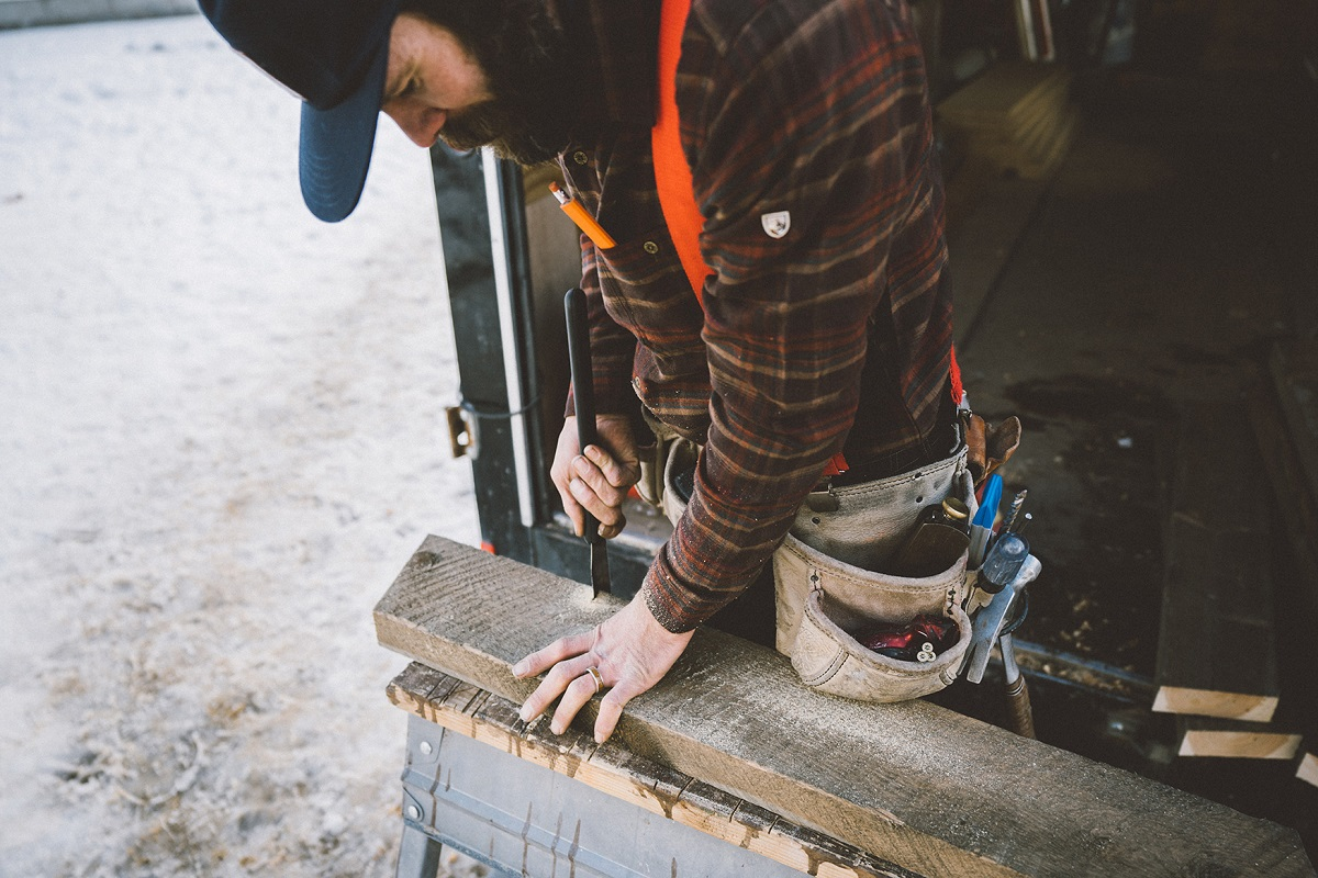 man in red plaid shirt working on a wooden plank
