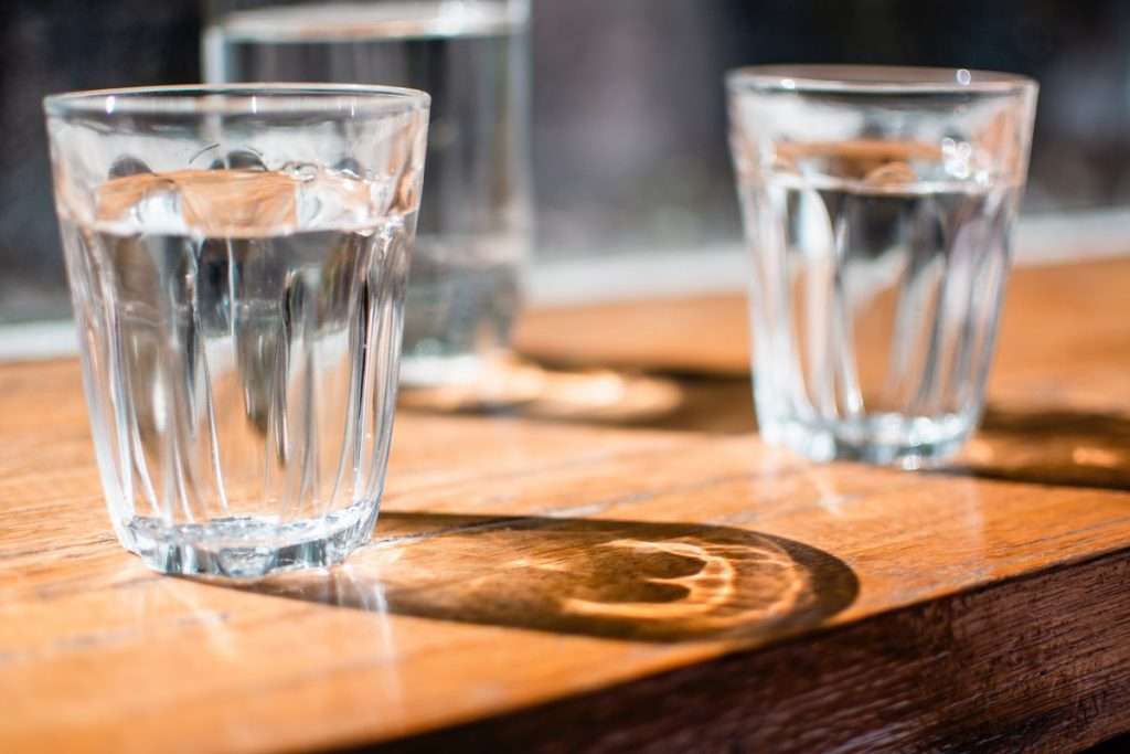 two glasses with water on the brown table