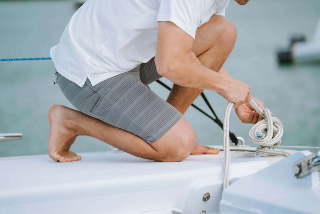 man kneeling on a boat holding rope knot