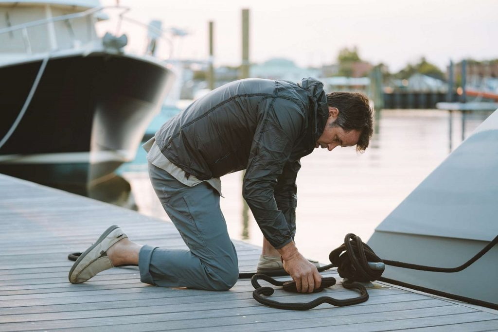 man tying up a boat to the dock