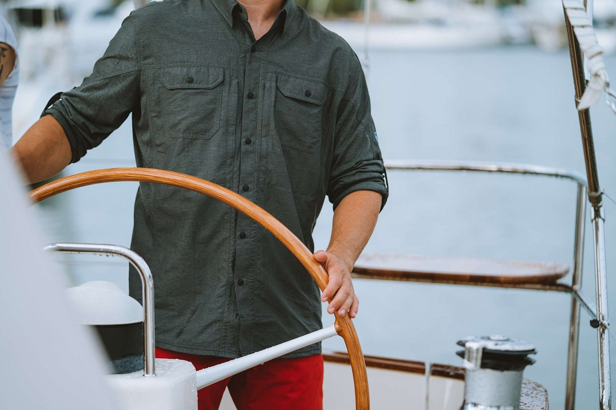 man in dark shirt holding boat wheel