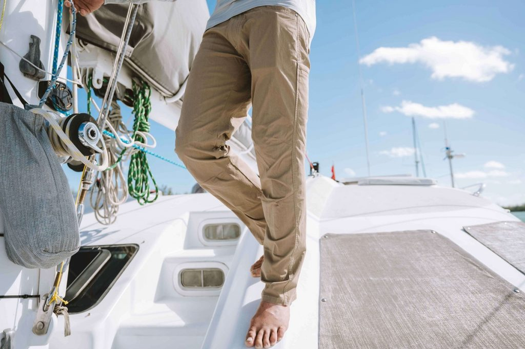 man in brown pants standing on a boat barefoot