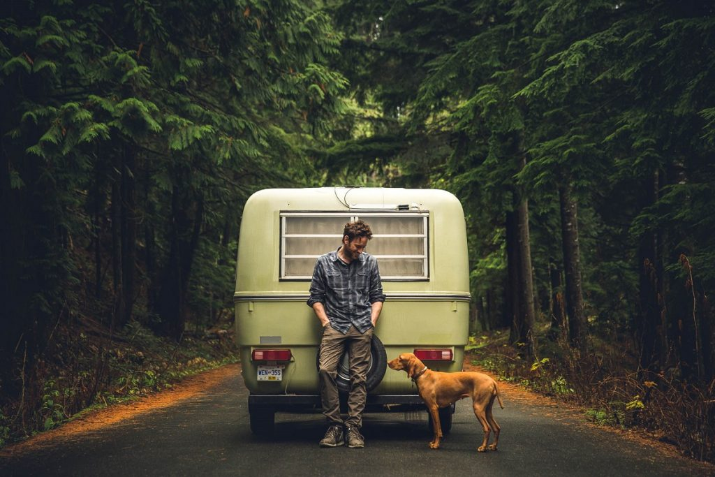 man and dog in front of camper