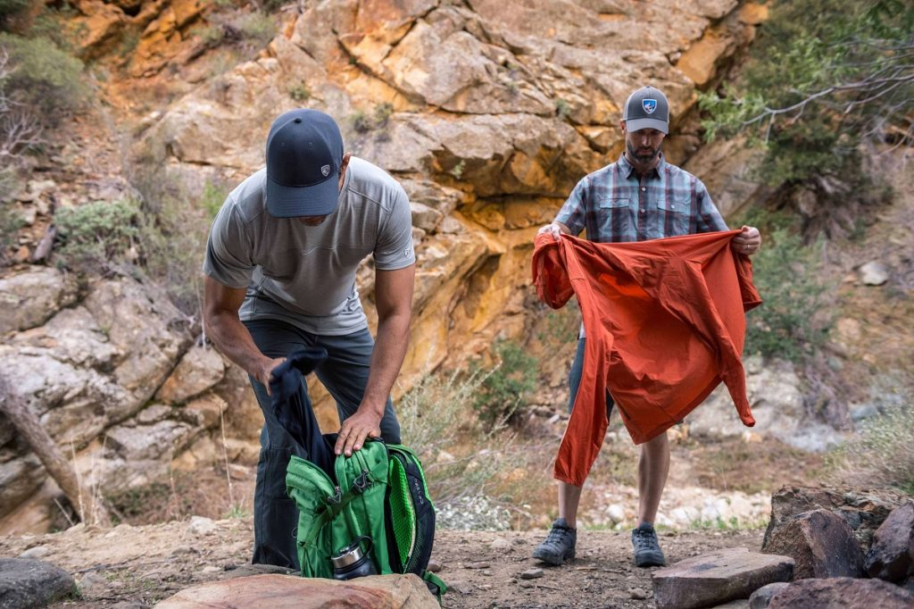 two men holding hiking gear