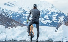 man on bike yellow bike in front of snowy mountain