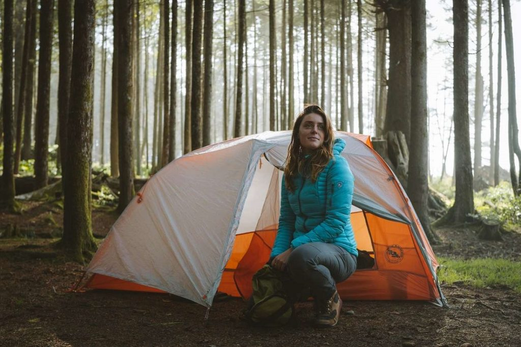 woman in blue jacket in front of orange tent in the woods