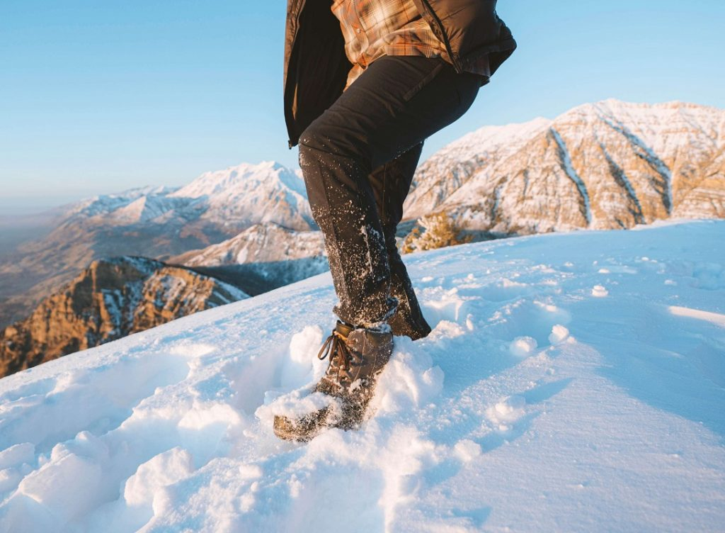 man in black pants standing on snow covered ground