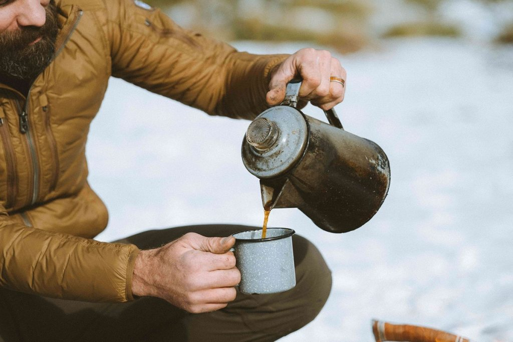 man in yellow jacket holding pot and mug on snowy ground