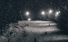 snowy ground with skiers in night with lights around