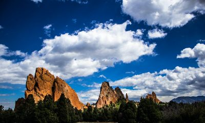 red rock formation under blue sky with white clouds