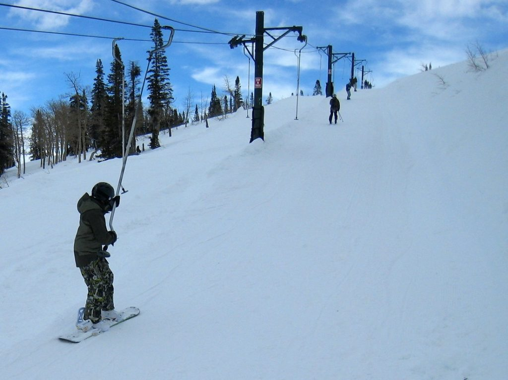 skier holding the ski lift on snowy grounds
