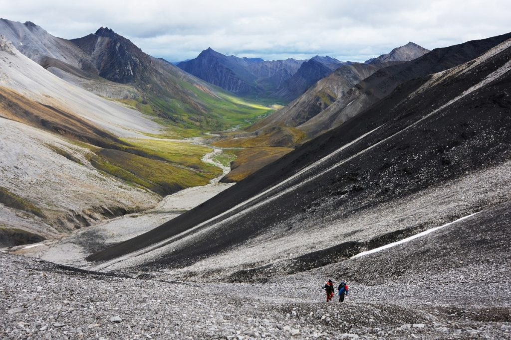 two people walking in front of mountains