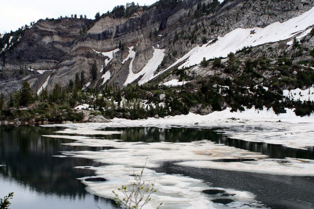 snow on body of water with snowy rock formations in the background