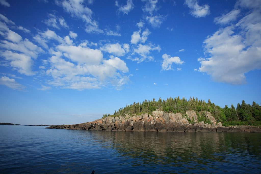 rocky island with trees on top surrounded by body of water during daytime