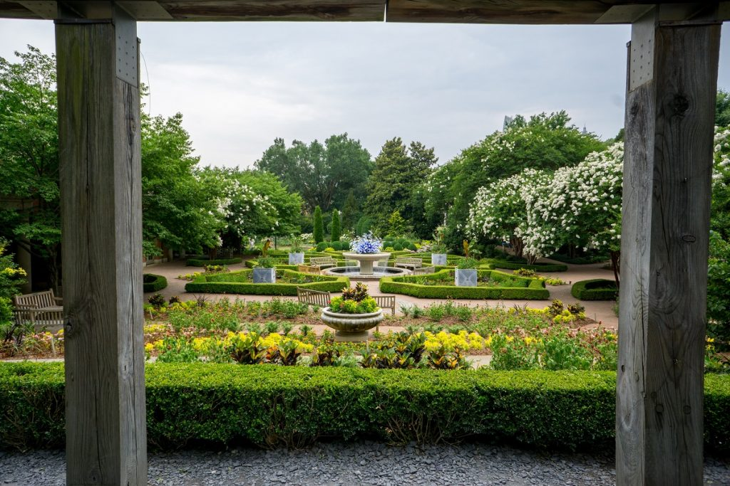 white fountain in middle of green plants trees and colorful flowers