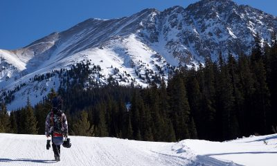 person walking on snow road facing mountain at daytime