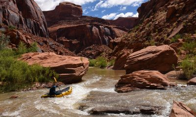 man in yellow raft on water between brown rock formations