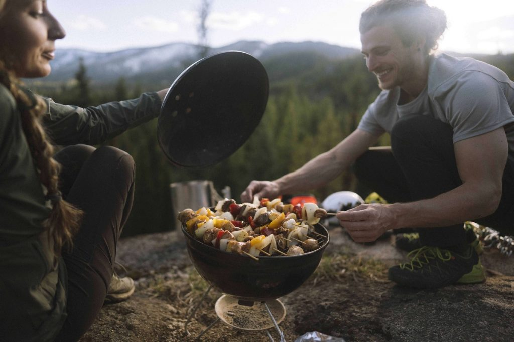 two climbers in KÜHL clothing grilling kebabs in outdoors