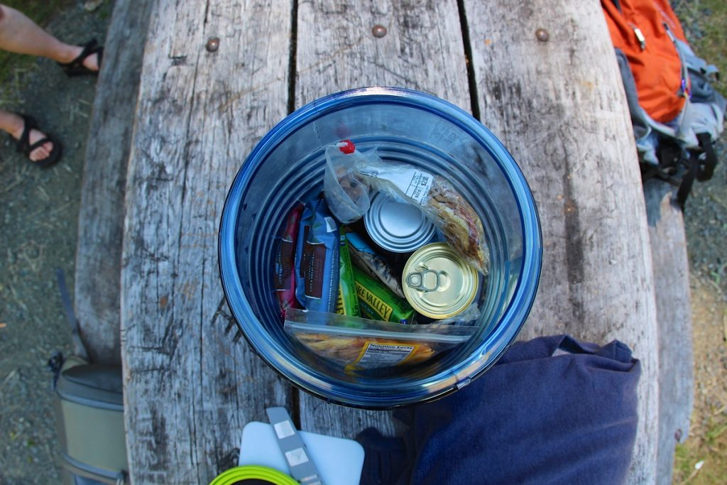 cans and bags in a round blue plastic box on table