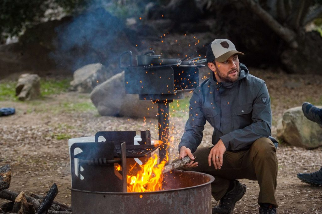 man standing next to a fired up outdoor grill