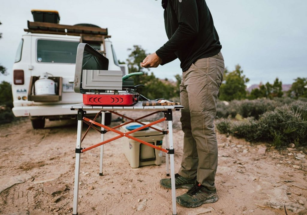 man standing next to table with portable stove outdoors