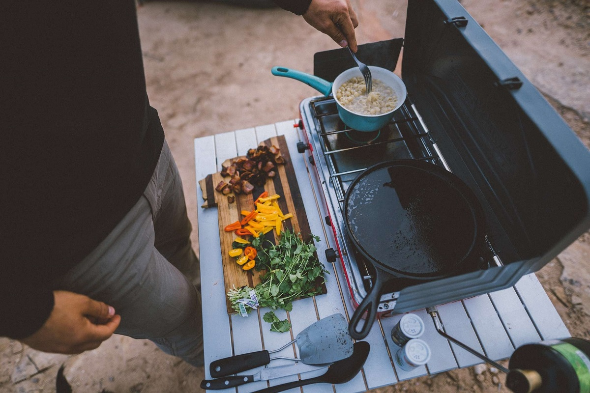man standing next to a table with camping stove with food pans