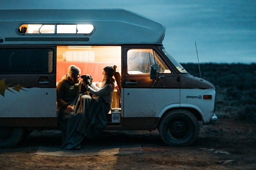 two people in KÜHL clothing RV camping with a dog during nighttime