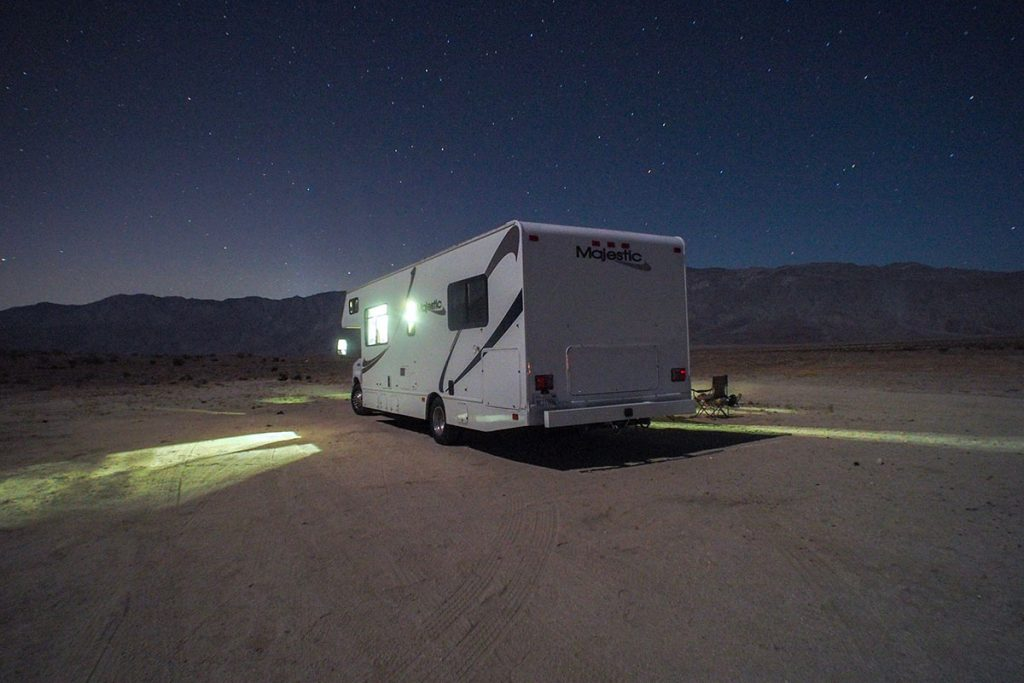 white rv in brown sand during night