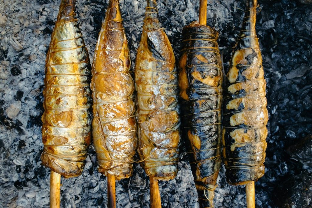 skewered fish cooking over campfire