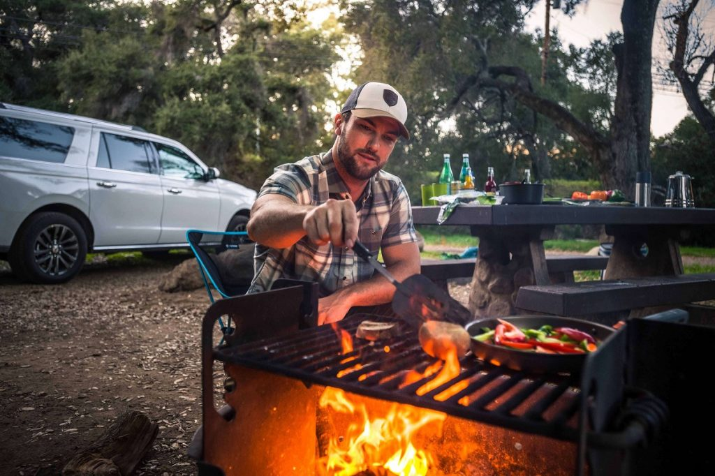 man in white hat and plaid shirt making food on camping grill