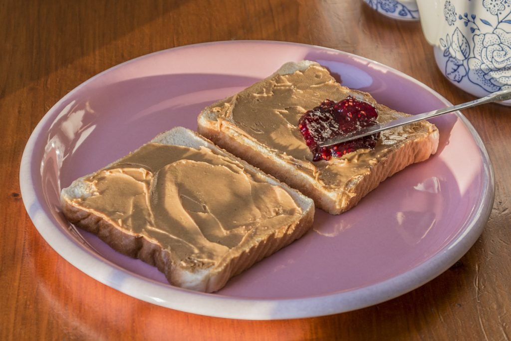 two pieces of bread on a pink plate with brown butter and jelly on them