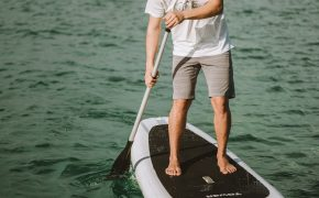man in KÜHL shorts paddleboarding on body of water