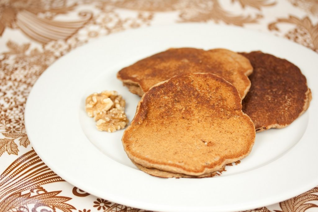 brown vegan pancakes with walnuts on white plate