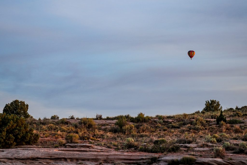 hot air balloon flying over field and rocks