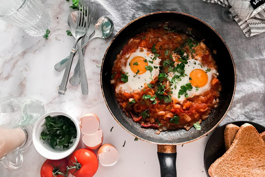 shakshuka eggs on black cooking pan next to fork and bread