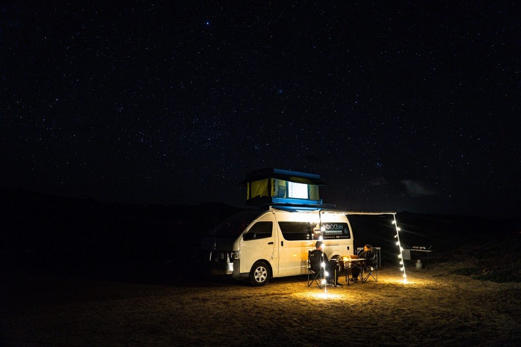 white RV on brown sand during nighttime