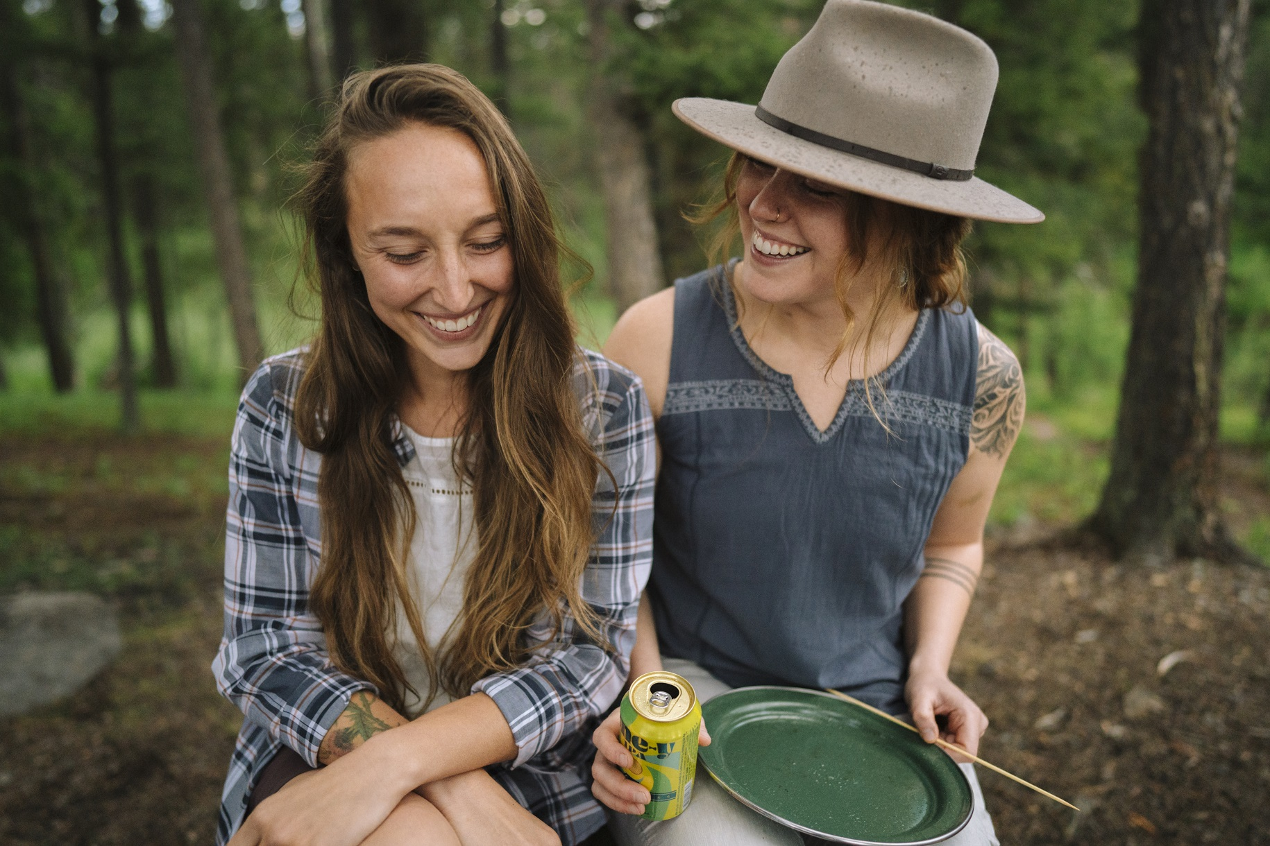 two women in KÜHL shirts smiling in the outdoors during daytime