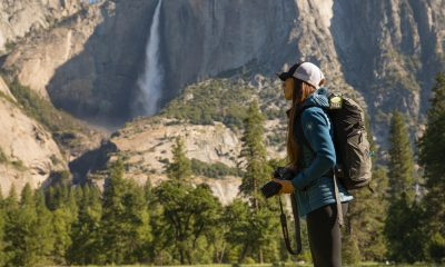 woman in blue KÜHL jacket holding camera in front of mountain with waterfall