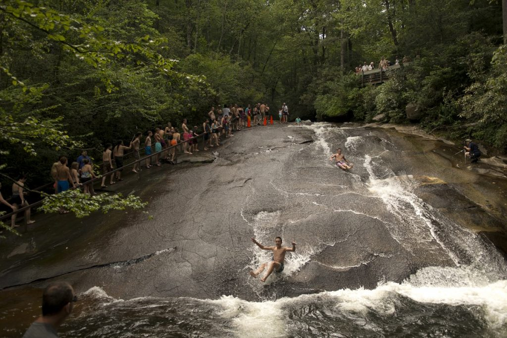 people sliding down the grey rock covered with water