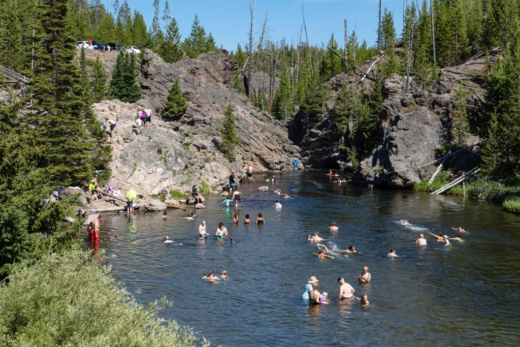 people swimming in body of water under mountain