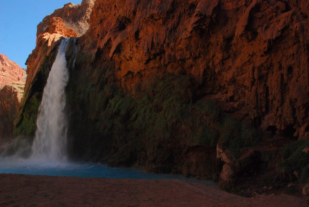 waterfall flowing from red rock formation