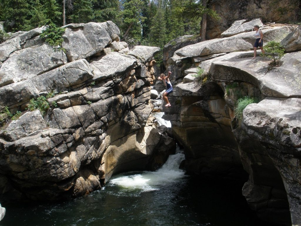 people jumping from a cliff into the water surrounded by rock formations