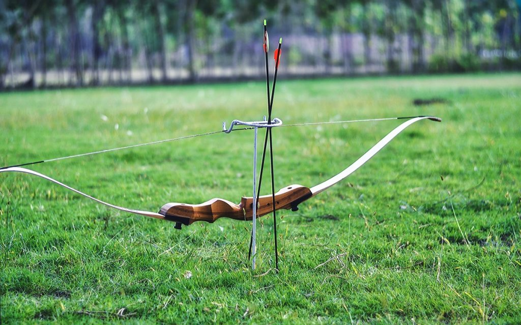 bow and arrows on green field during daytime