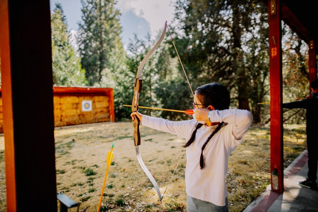 girl in white shirt holding brown bow and arrow