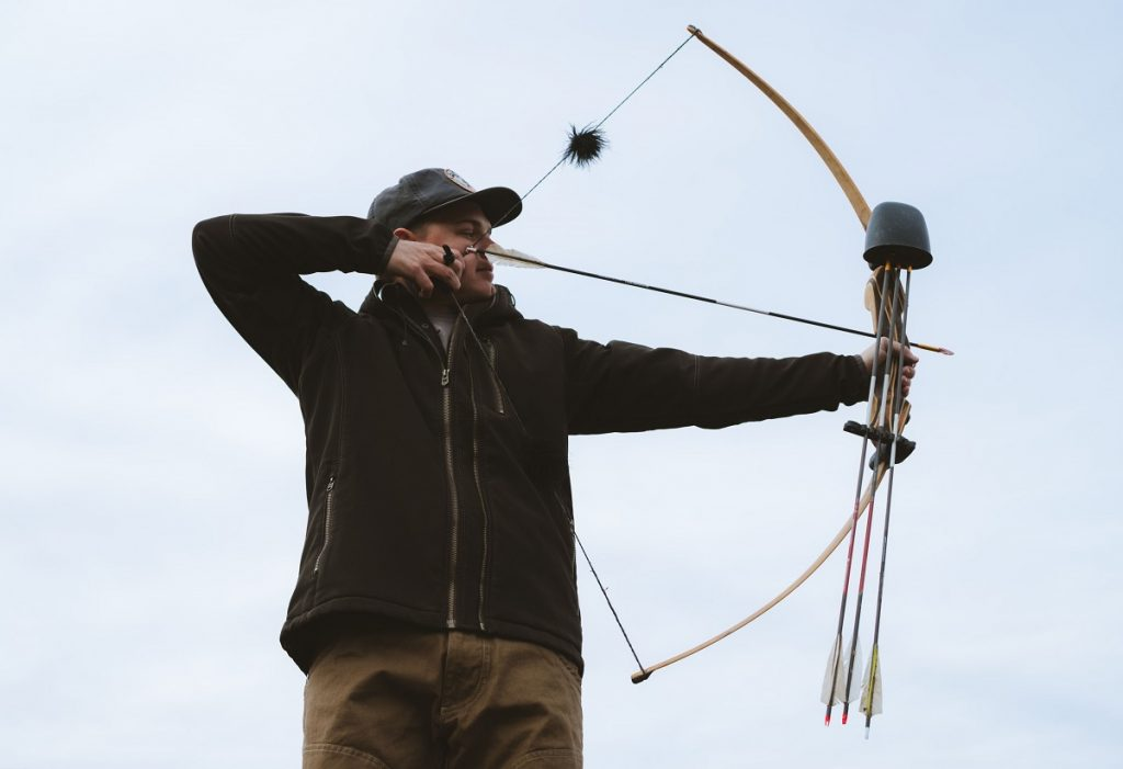 man in KÜHL jacket and KÜHL pants aiming with bow and arrow