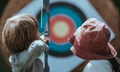 boy aiming bow on target while girl with red hat watches