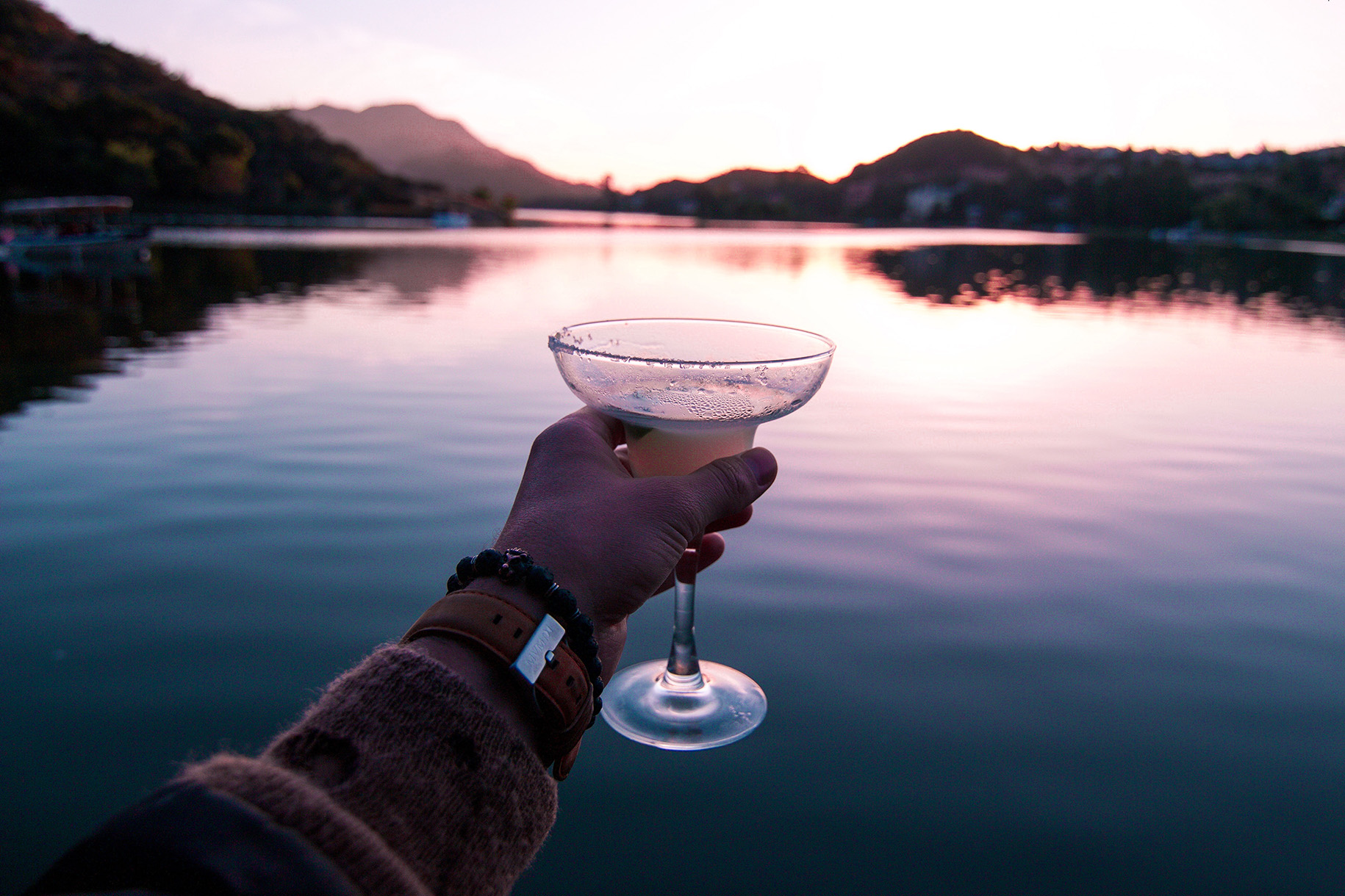 man holding glass in front of body of water at dusk